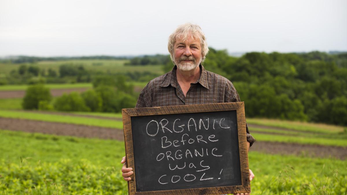 Amy's man holding organic sign